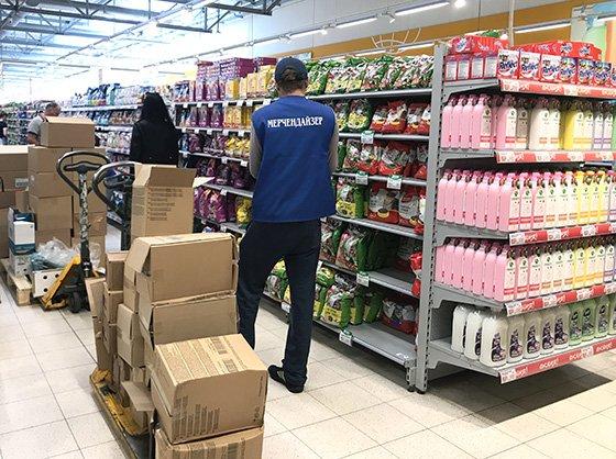 мерчендайзер в магазине раскладывает товар на полках
